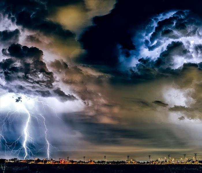 image of thunderstorm taking place over a city and water at nigt