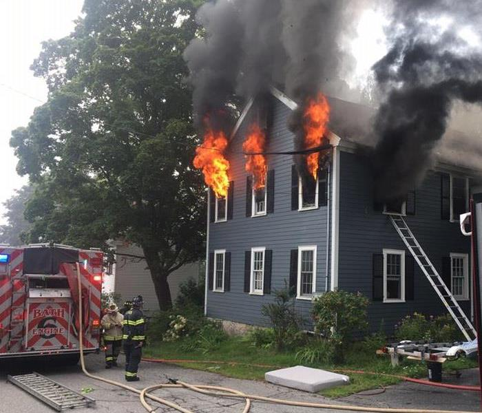 Flames billowing from a two story  style house on fire